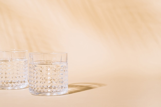Verre D'eau Sur Pastel Avec Ombre Dure Photo Premium