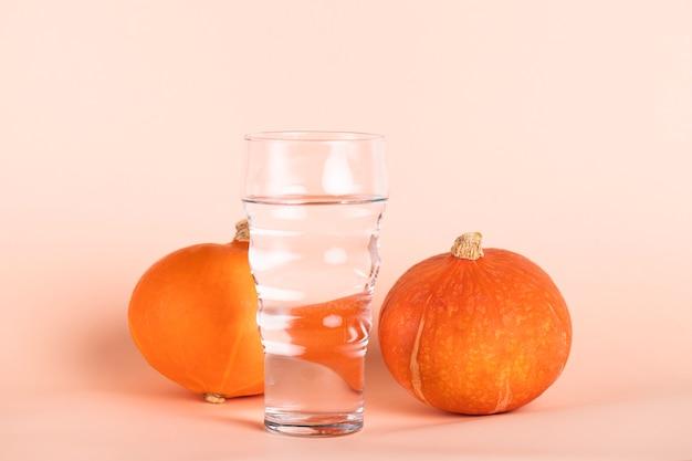 Verre d'eau avec petites citrouilles Photo gratuit