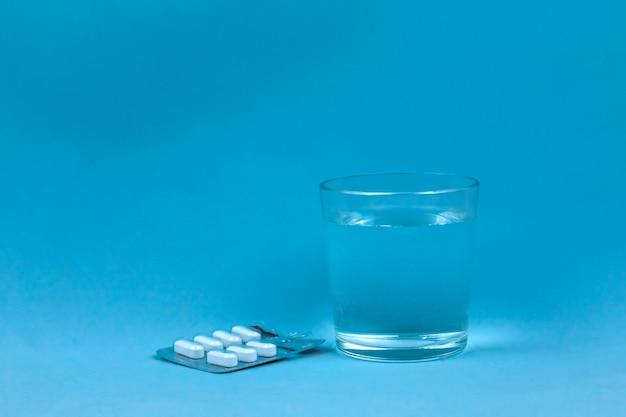 Verre d'eau et des pilules sur fond bleu Photo Premium