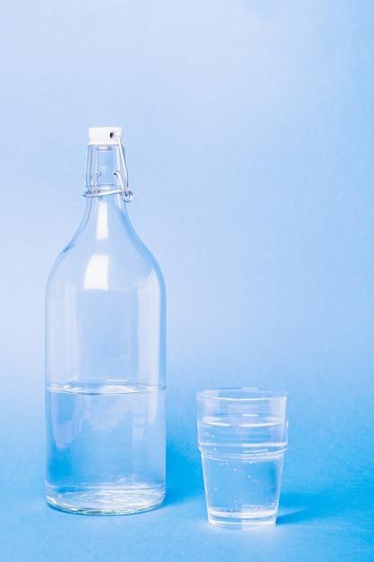 Verre Avec De L'eau Près De La Bouteille Sur Bleu Photo Premium