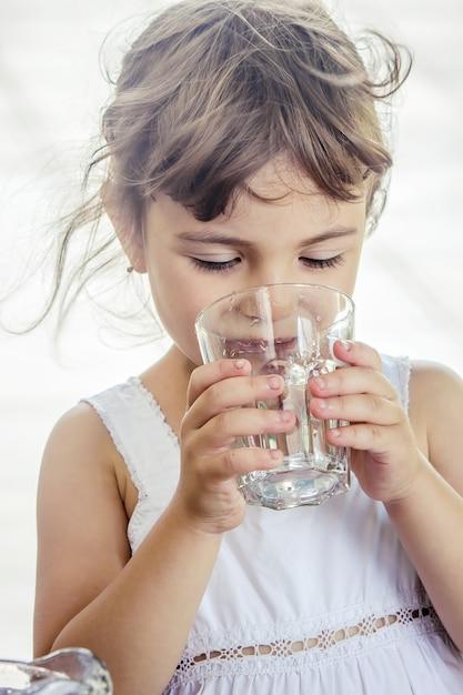 Verre d'enfant d'eau. mise au point sélective. boisson. Photo Premium