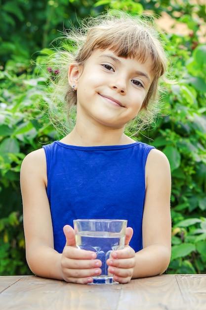 Verre d'enfant d'eau. mise au point sélective. la nature. Photo Premium
