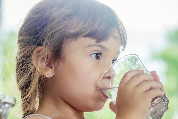 Verre d'enfant d'eau. mise au point sélective. Photo Premium