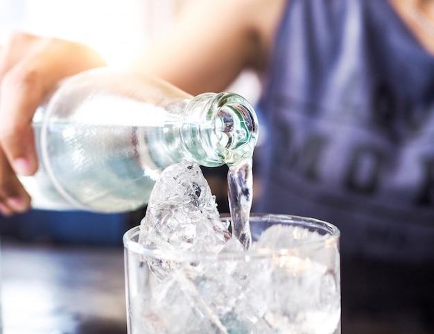 Verre avec de la glace et les mains versent de l'eau potable rafraîchissant et étanchent la soif en été Photo Premium