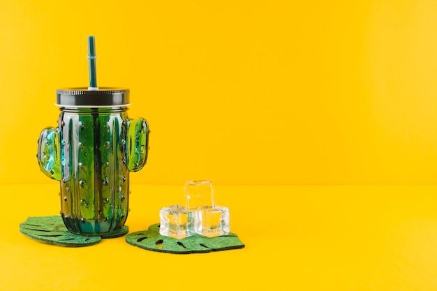 Verre de jus de cactus en verre et des glaçons en cristal sur des dessous de verre sur fond jaune Photo gratuit