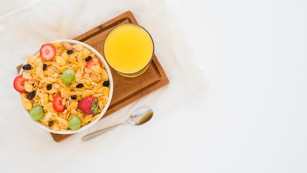 Verre De Jus De Mangue Et Cornflakes Aux Fruits Dans Un Bol Blanc Sur Une Planche à Découper Au Fond Blanc Photo gratuit