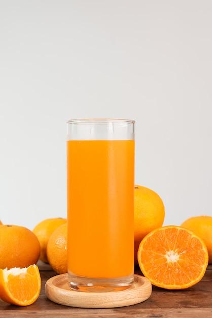 Verre de jus d'orange frais et fruits sur une table en bois Photo Premium