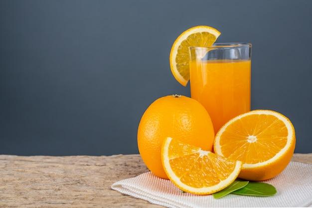 Verre de jus d'orange posé sur du bois. Photo gratuit
