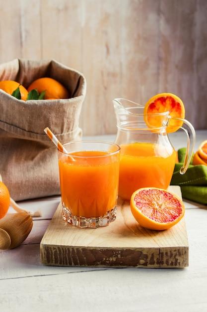 Verre De Jus D'orange Pressé Frais Et Oranges Sanguines Sur Table En Bois. Photo Premium