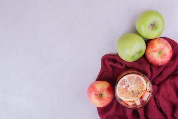 Un Verre De Jus De Pommes Sur Une Serviette Rouge Photo gratuit