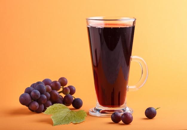 Verre de jus de raisin rouge sur fond orange. vue de côté Photo Premium