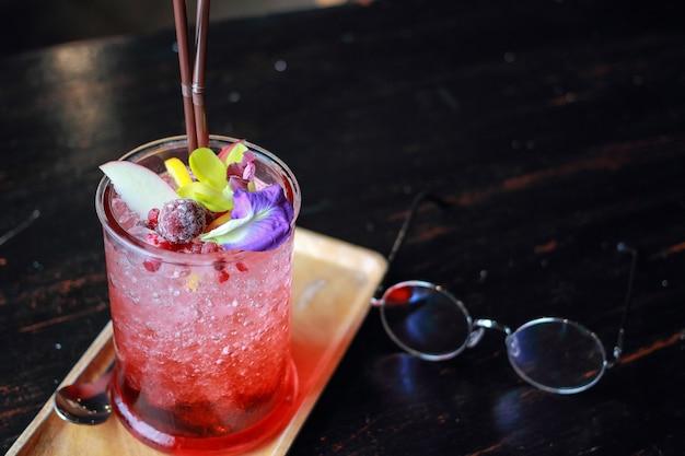 Un verre de jus rouge et de fruits sur la table. Photo Premium