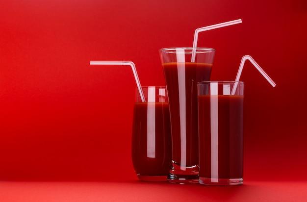 Verre de jus de tomate isolé sur fond rouge Photo Premium