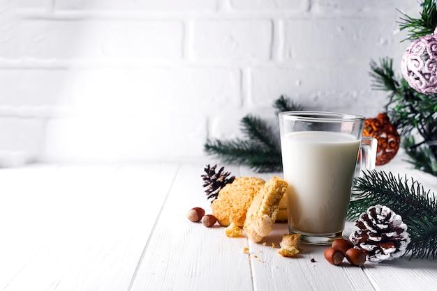 Verre de lait et des biscuits laissés spécifiquement pour le père noël. Photo Premium