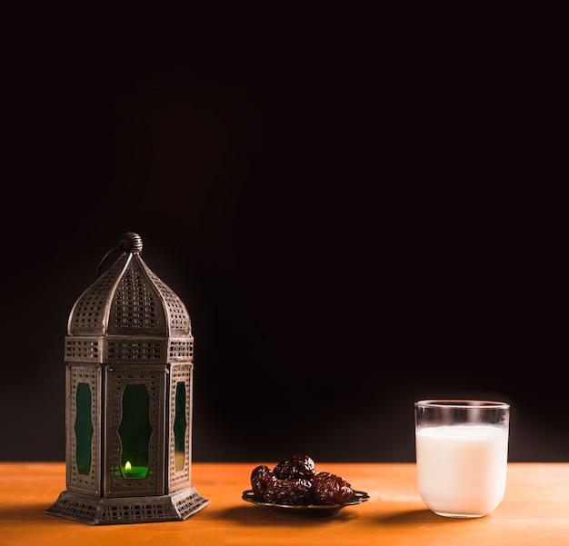 Verre de lait près de soucoupe avec pruneaux et lanterne Photo gratuit