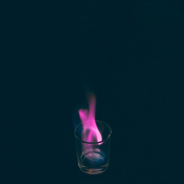 Verre à liqueur tequila brûlant avec flamme rose Photo gratuit