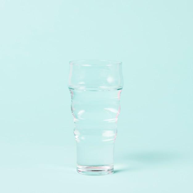 Verre minimaliste d'eau sur fond bleu Photo gratuit