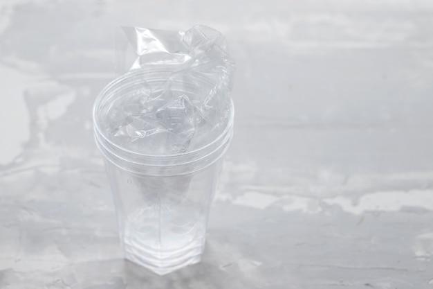 Verre En Plastique Avec Du Plastique Sur Fond En Céramique Photo Premium
