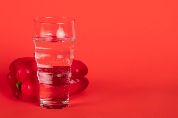 Verre avec poivron rouge et fond rouge Photo gratuit