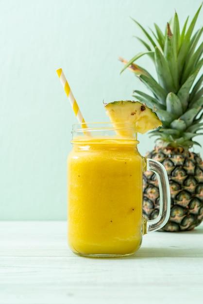 Verre à smoothie d'ananas frais sur une table en bois Photo Premium