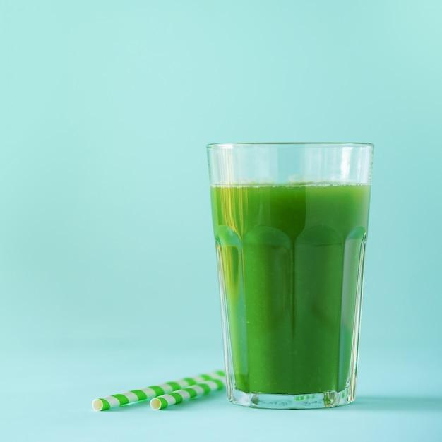 Verre de smoothie au céleri vert sur fond bleu Photo Premium