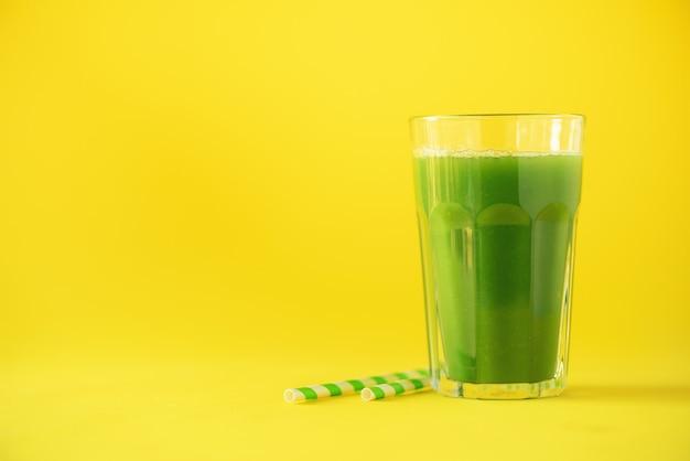 Verre de smoothie au céleri vert sur fond jaune Photo Premium