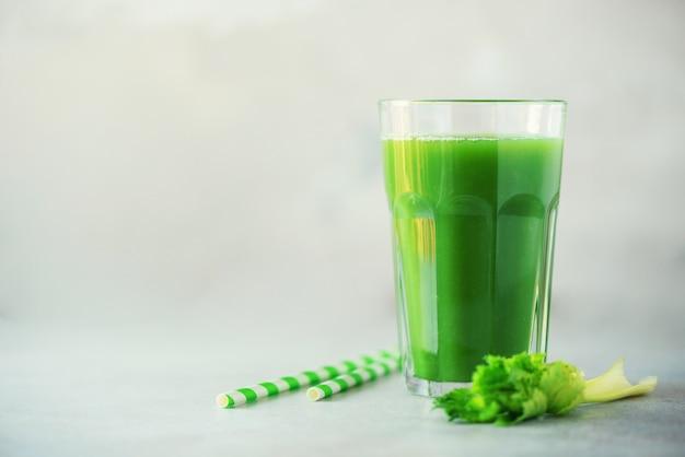 Verre de smoothie de céleri vert sur fond de béton gris Photo Premium