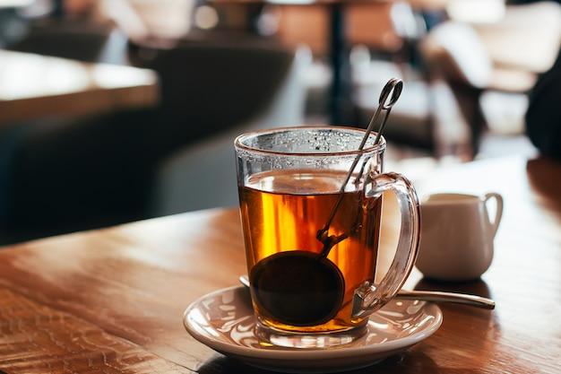 Verre tasse de thé chaud dans un café avec un arrière-plan flou lumière naturelle Photo Premium