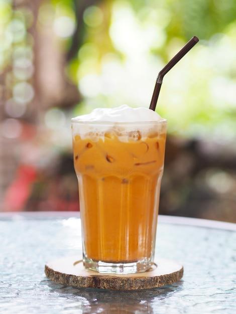 Verre de thé au lait thaïlandais avec crème fouettée sur le dessus et paille au café. Photo Premium