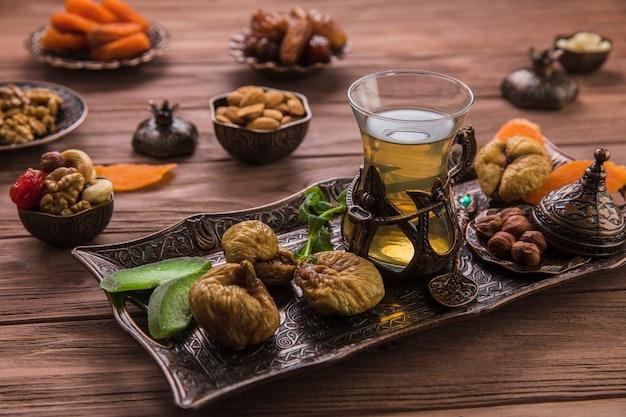 Verre à thé avec figues séchées et noix sur le plateau Photo gratuit