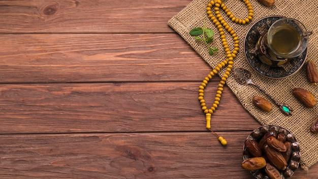 Verre à thé avec fruits de dattes et perles sur toile Photo gratuit