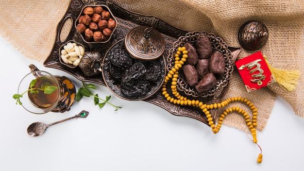 Verre à thé avec fruits secs et perles sur toile Photo gratuit