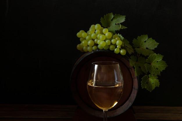 Un verre de vin blanc, une grappe de raisin avec des feuilles et un tonneau de vin Photo Premium
