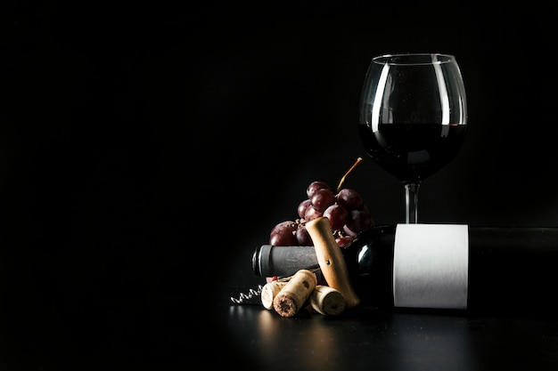 Verre à vin et bouteille près de tire-bouchon et de raisin Photo gratuit
