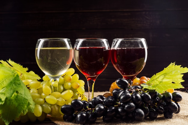 Verre à vin et grappe de raisin sur table en bois Photo Premium