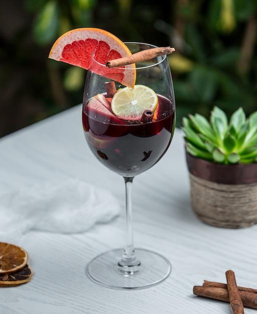 Verre à vin avec pamplemousse à la cannelle et autres fruits Photo gratuit