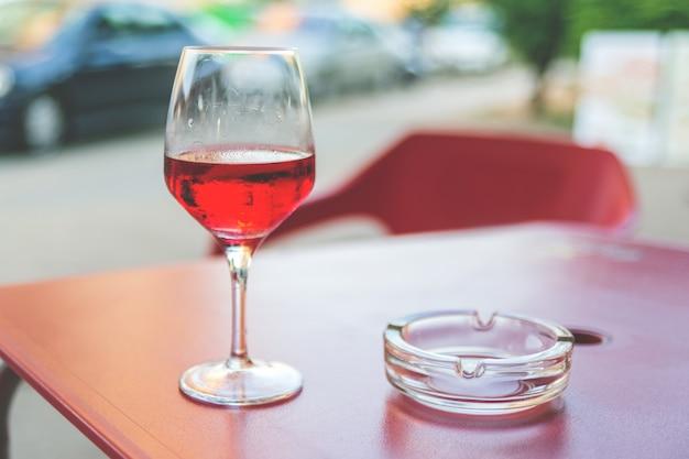 Verre de vin rosé sur la table dans le café de rue tonification vintage mise au point sélective Photo Premium