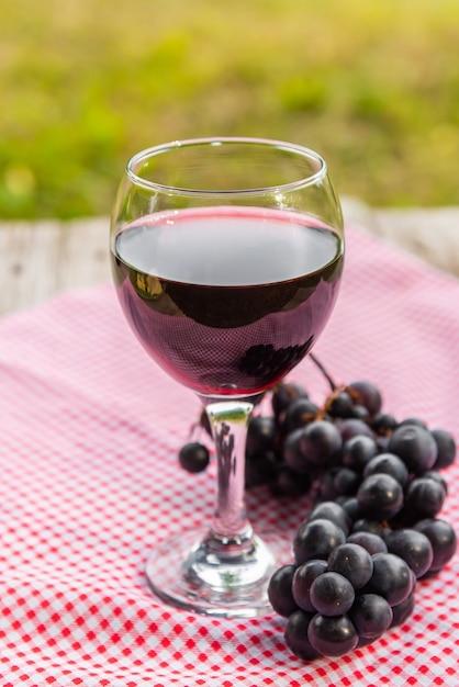 Un Verre De Vin Rouge Avec Une Grappe De Raisin. Photo Premium