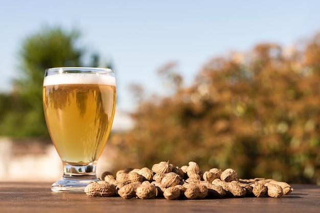 Verre De Vue Côté Avec De La Bière à Côté De Cacahuètes Sur La Table Photo gratuit