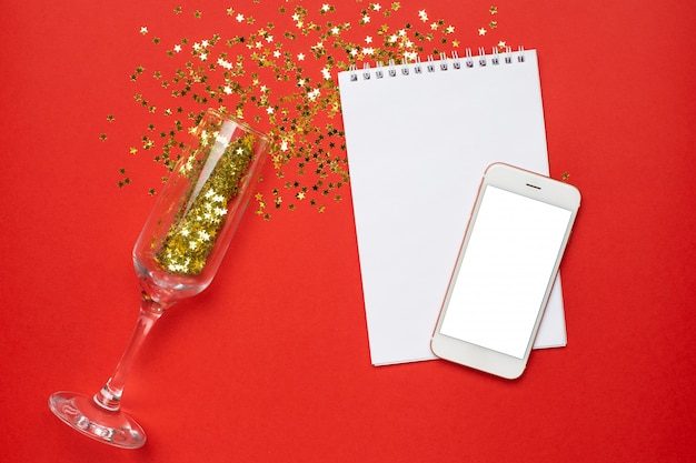 Verres à champagne, bloc-notes et téléphone mobile avec concept de confettis, étoiles de noël et nouvel an des étoiles d'or Photo Premium