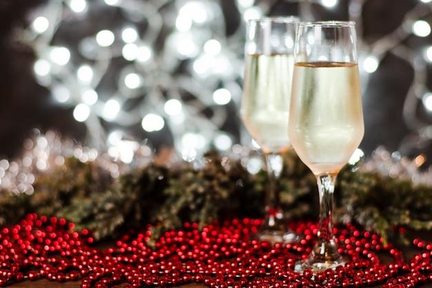 Verres de champagne avec des lumières de noël en arrière-plan Photo gratuit