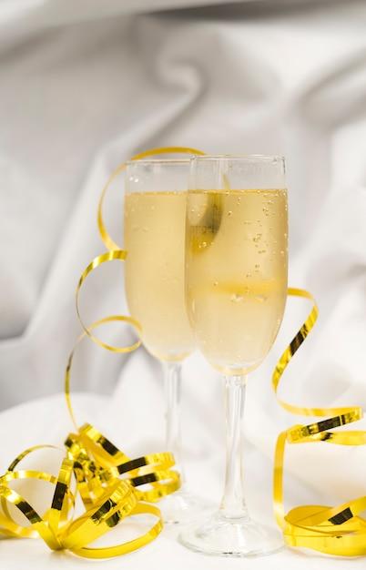 Verres De Champagne Rafraîchissant Avec Des Banderoles Dorées Sur Un Drap Blanc Photo gratuit