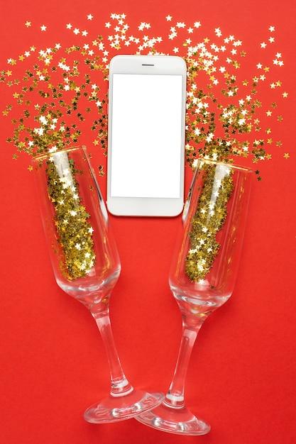 Verres à champagne et téléphone portable avec concept confetti, noël et nouvel an des étoiles d'or Photo Premium