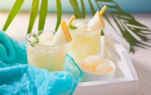 Verres à cocktail au melon sur une table blanche avec la feuille de palmier à thème tropical Photo Premium