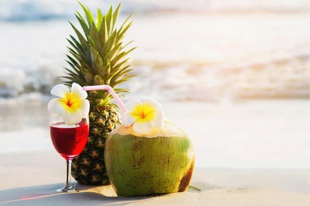 Verres à Cocktail à La Noix De Coco Et à L'ananas Sur Une Plage De Sable Fin - Fruits Et Boisson à La Plage De La Mer Photo gratuit