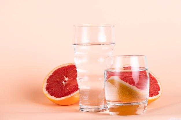 Verres d'eau de tailles différentes avec des oranges rouges Photo gratuit