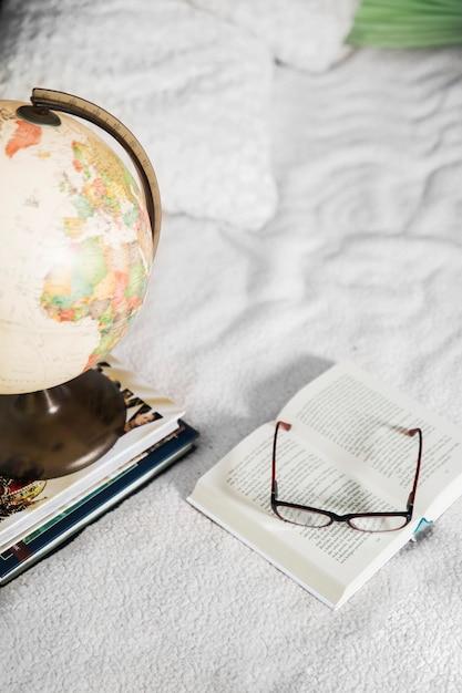 Verres et globe près des livres Photo gratuit