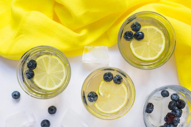 Verres de jus de citron avec des myrtilles et des glaçons sur fond blanc Photo gratuit