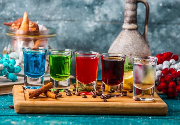 Verres à liqueur avec boissons colorées sur planche de bois Photo gratuit