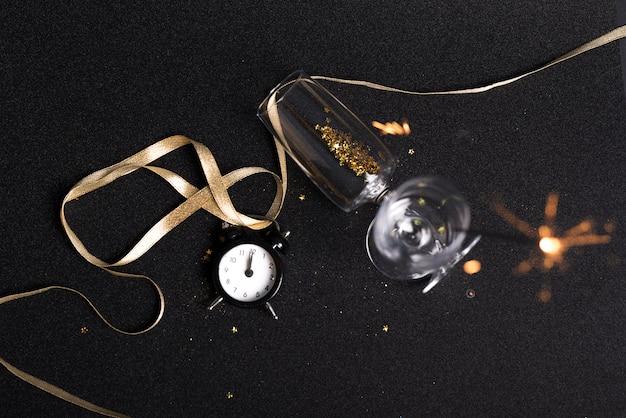 Verres à paillettes et feu du bengale sur table Photo gratuit